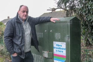 David Walker campaiging for better broadband by a BT cabinet in West Felton