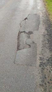 A previously repaired pothole. The old white paint can be seen as can the rectangle cut out. Lack of sealing has allowed water into the joints and allowed the repair to break out again and expand