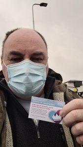 David brandishing his vaccination card outside the Orthopaedic