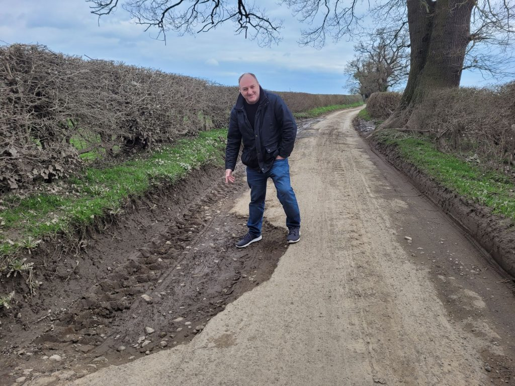 David examining the half the lane has gone in Hindford. The whole pockmarked section of lane is appalling and dangerous